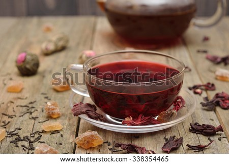 Hibiscus tea in a glass cup on a wooden background - stock photo