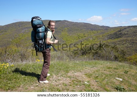 Hicker girl with backpack in mountains