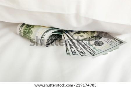 Hidden money under pillow close up - stock photo