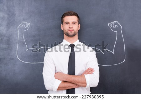 Hidden possibilities. Handsome young man in shirt and tie looking at camera and keeping arms crossed while standing against chalk drawing of muscular arms - stock photo