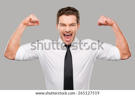 Hidden possibilities. Handsome young man in shirt and tie looking at camera and showing his biceps while standing against grey background - stock photo