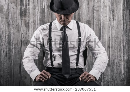 Hidden threat. Bossy senior man in gangster clothing sitting at the chair and against a wall  - stock photo