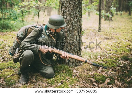 Hidden unidentified re-enactor dressed as World War II german wehrmacht soldier sitting with rifle in an ambush in forest.