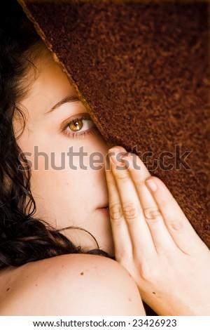 Hidden woman staring at camera - stock photo