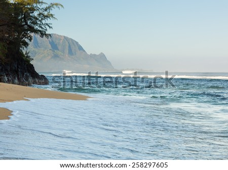 Hideaways Beach near Hanalei in Kauai with the Na Pali mountain range in the background. Rough seas crash against shore at Hanalei, Kauai, Hawaii - stock photo