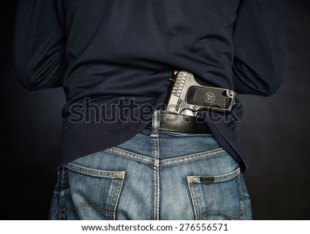 Hided handgun under the denim belt. - stock photo