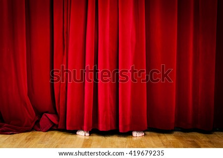 Hiding behind Red Curtain - stock photo