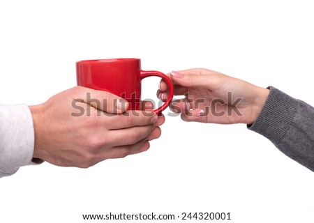 Hiding from winter at home. Closeup image of a red cup of tea passing from one hand to another isolated on white background - stock photo