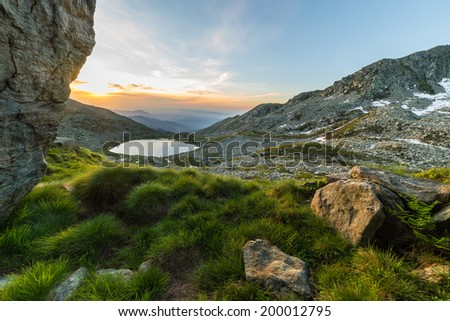High altitude mountain lake at sunrise with rocks and grass in the foreground. Location: Italian Alps in Orsiera Regional Park, Piedmont. - stock photo