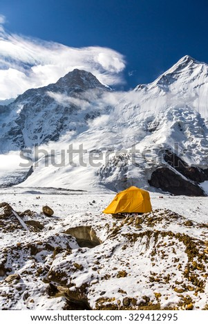 High Altitude Mountains and One Orange Tent Steep Snowbound Peaks Bivouac Assembled on Rocky Moraine of Glacier - stock photo