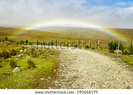 HIGH ALTITUDE ROAD WITH RAINBOW IN ANDES MOUNTAINS   - stock photo