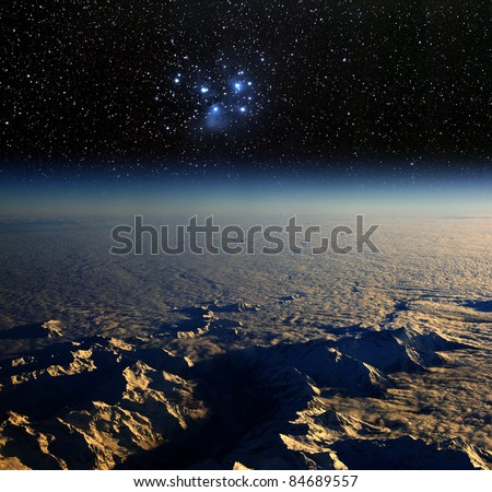High altitude view of the Earth in space. and the Pleiades star cluster.