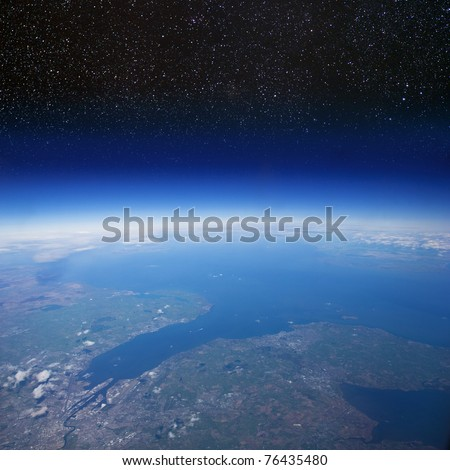 High altitude view of the Earth in space (the city in the foreground is Belfast in Northern Ireland) - stock photo