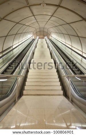 High and large staircase and double escalator in underground passage - stock photo