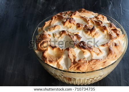 High angel view of homemade banana pudding with Meringue made from scratch over a rustic dark background.