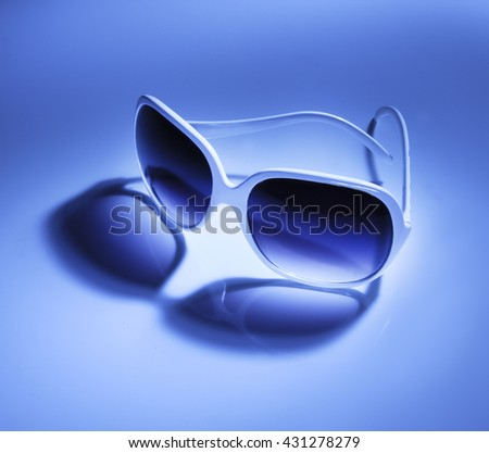 HIGH ANGLE , BEAUTIFUL COLORFUL IMAGE OF WHITE SUNGLASSES WITH YELLOW AND BLUE LIGHT  - stock photo