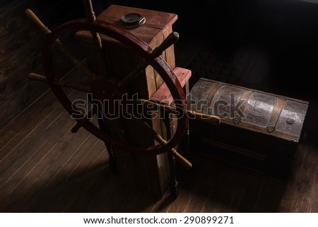 High Angle Chiarascuro of Antique Steering Helm with Wheel and Compass on Deck of Sailing Ship with Old Wooden Chest - stock photo