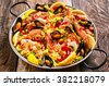 High Angle Close Up of Colorful Seafood Spanish Paella Rice Dish with Shrimp and Mussels Shellfish Garnished with Fresh Lemon and Served in Pan with Green Linen Napkin on Rustic Wooden Table - stock photo