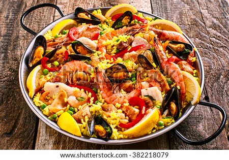 High Angle Close Up of Colorful Seafood Spanish Paella Rice Dish with Shrimp and Mussels Shellfish Garnished with Fresh Lemon and Served in Pan with Green Linen Napkin on Rustic Wooden Table