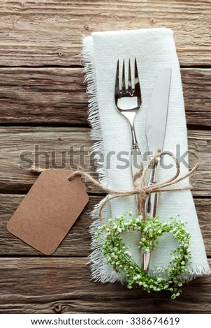 High Angle Close Up of Silver Wedding Knife and Fork Tied with String and Blank Tag on White Napkin with Fringed Edges and Heart Shaped Wreath Made from Greenery and Small White Flowers - stock photo