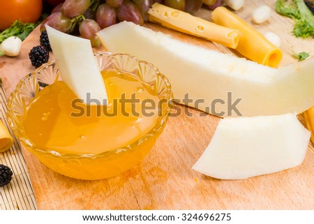 High Angle Close Up View of Gourmet Cheese and Fruit Board with Dish of Fruit Preserves for Dipping - stock photo