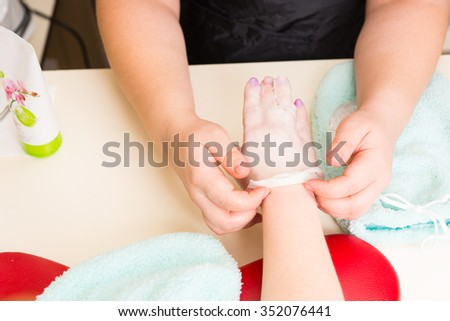 High Angle Close Up View of Manicurist Peeling Dried Wax Layer from Hands of Female Client During Paraffin Wax Spa Treatment