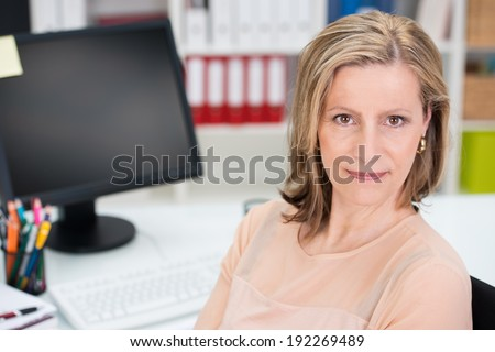 High angle close up view of the face of an attractive smiling middle-aged businesswoman sitting at her desk in her office - stock photo
