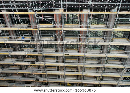 High angle close up view of the front facade of a highrise multi-story building under construction or renovation with scaffolding - stock photo