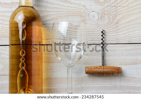 High angle closeup of a bottle of white wine next to a wineglass and corkscrew on a whitewashed rustic table. Horizontal format. - stock photo