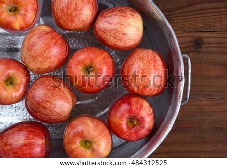 High angle closeup of a metal tub filled with water and apples for the Halloween custom of Apple Bobbing.