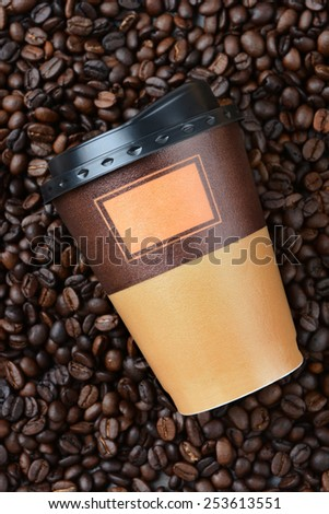 High angle closeup shot of a disposable coffee cup laying on fresh roasted coffee beans. The beans fill the frame. - stock photo