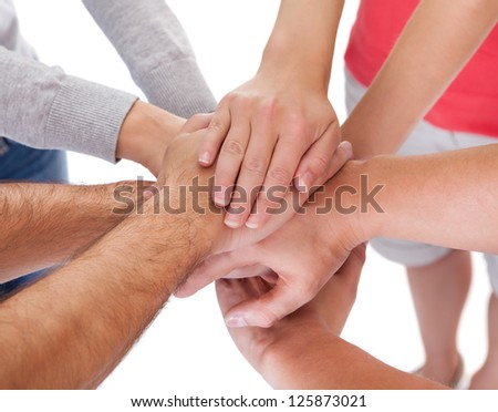 High angle conceptual teamwork and cooperation image of four casual middle-aged friends isolated on white