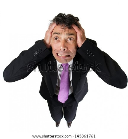 High angle full length portrait of an expressive anxious businessman tearing at his hair isolated on white - stock photo