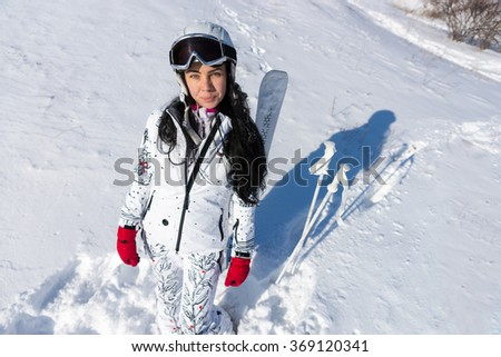 High Angle Full Length View of Young Woman Wearing White Ski Suit and Helmet Standing on Snow Covered Mountainside with Skis and Poles on Sunny Day with Warm Sunshine