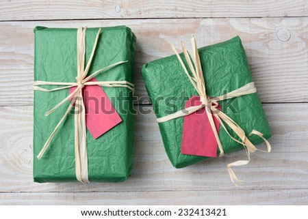 High angle image of two green Christmas presents on a rustic white wood table. Wrapped with crumpled tissue paper and tied with raffia both have blank red gift tags. Horizontal format. - stock photo