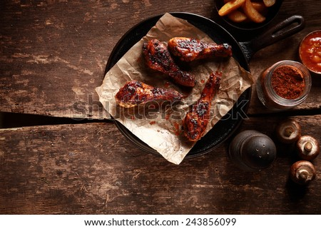 High Angle Looking Down at Saucy Barbecued Chicken Drumsticks on Cast Iron Pan Accompanied by Spices and Ingredients - stock photo