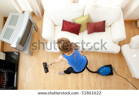 High angle of a blond woman vacuuming in the living-room - stock photo