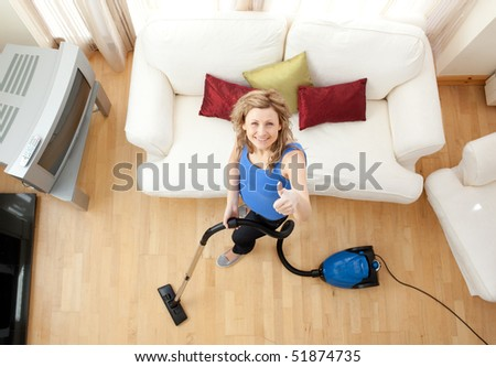 High angle of a cheerful woman vacuuming in the living-room - stock photo