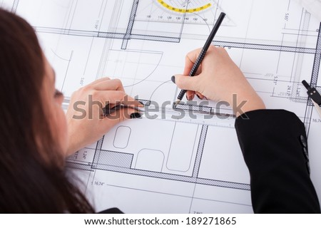 High angle of businesswoman making blueprint at desk in office - stock photo