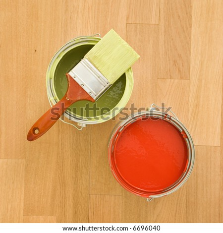 High angle of paintbrush with paint cans on wood floor.