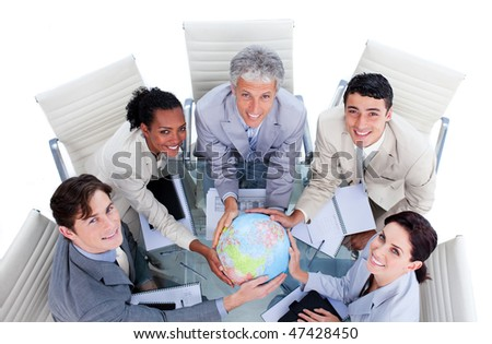 High angle of positive business people holding a terrestrial globe in a meeting - stock photo