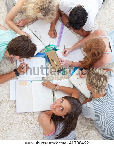 High angle of teenagers lying on the ground studying together - stock photo