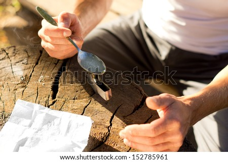 High angle of the hands of a man heating soluble drug in a teaspoon above the flame of a lighter - stock photo