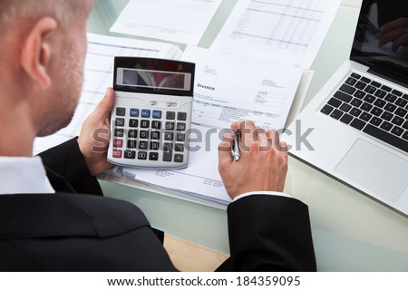 High angle over the shoulder view of a businessman checking figures in a report looking down onto the calculator and paperwork - stock photo