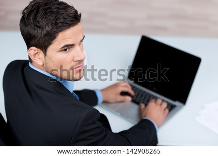 High angle over the shoulder view of a determined handsome young businessman typing on his laptop computer with the blank screen visible to the camera - stock photo