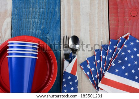High angle photo of a Fourth of July picnic table setting. The red white and blue items are on a wood table painted for the holiday. - stock photo