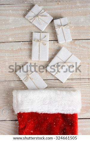 High angle photo of five Christmas presents wrapped in white paper and tied with white string and a stocking. The gifts are on a whitewashed wood table. Vertical with Snow effect. - stock photo