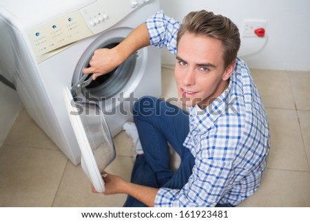 High angle portrait of a technician repairing a washing machine