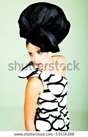 High angle portrait of a young woman. She is wearing a large hat and a black and white dress with a bow on the shoulder. Vertical shot. - stock photo