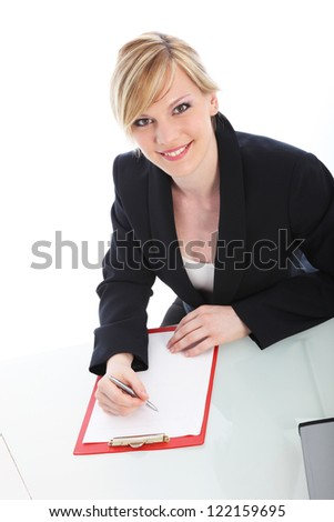 High angle portrait of an attractive young businesswoman writing on a blank sheet of paper on a clipboard and smiling up at the camera isolated on white - stock photo